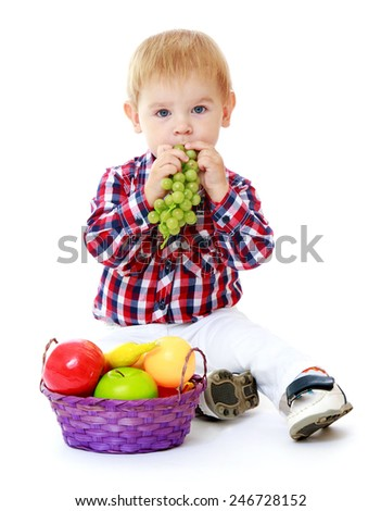 Little boy playing with fruits sitting on the floor.Isolated on white background