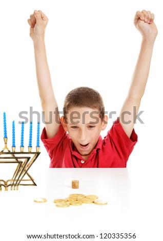 Little boy playing with his dreidel on Hanukkah.   White background. - stock photo