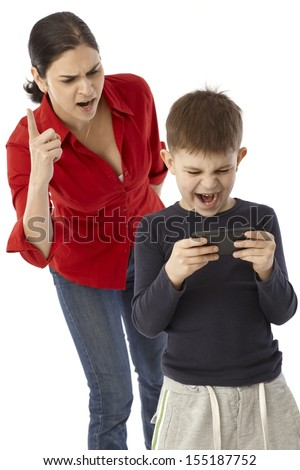 Little boy playing with mother's mobilephone, angry mother warning with finger. - stock photo