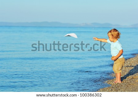 Little boy playing with paper airplane on the beach - stock photo