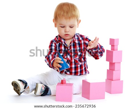 Little boy playing with pink cubes.White background, isolated photo. - stock photo
