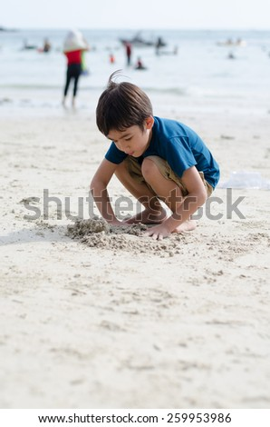 Little boy playing with sand at the beach