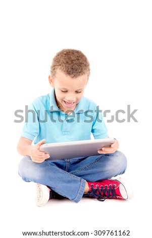 little boy playing with tablet isolated in white - stock photo