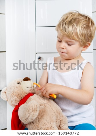 Little boy playing with teddy bear toy and brushing teeth