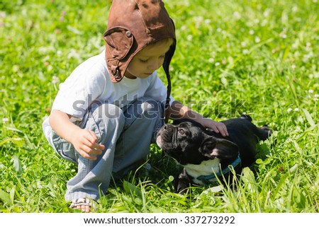 Little boy playing with the dog French Bulldog outdoors - stock photo