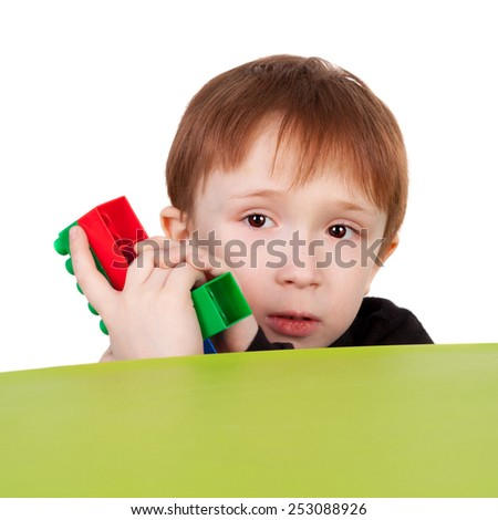 little boy playing with the pistol made with the bricks  - stock photo