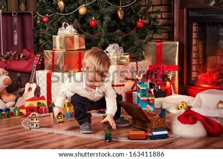 Little boy playing with toys at home near the fireplace and Christmas tree. - stock photo