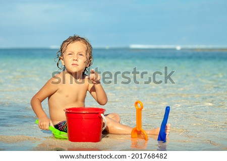 little boy playing  with toys sand set  on the beach at the day time
