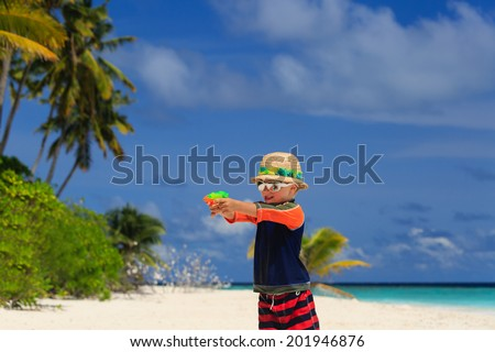 little boy playing with water guns on tropical beach - stock photo