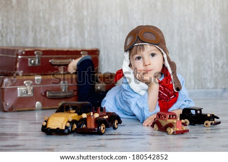 Little boy, playing with wooden cars, indoor, suitcases behind him - stock photo