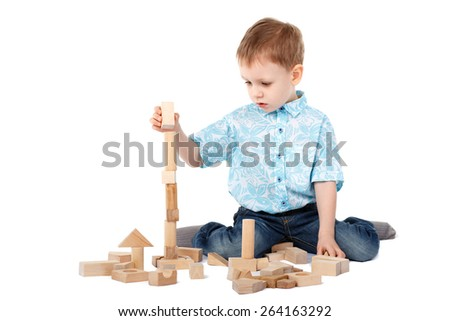 Little boy playing with wooden designer on the floor isolated on white background - stock photo