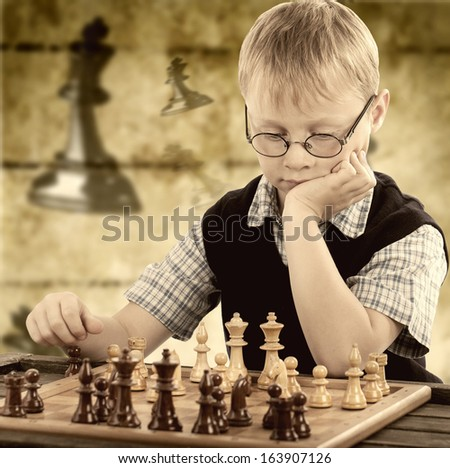 little boy plays chess, rustic chess background  - stock photo