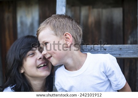 Little boy plays with his older sister in outdoors. - stock photo