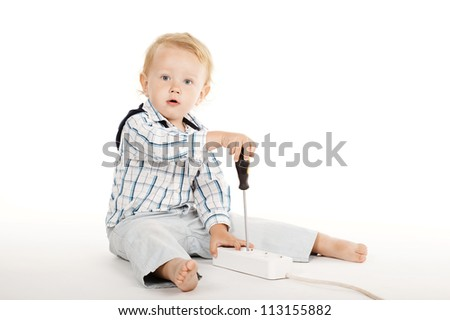 little boy plays with plug and screwdriver - stock photo