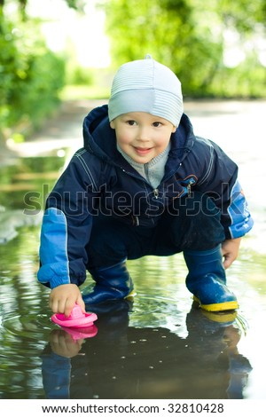 little boy plays with ship in the puddle - stock photo