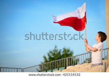 Little boy - Polish football team fan - supporter with Polish flag on the stadium - stock photo