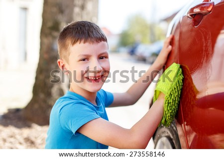Little boy polish red car, teeth smile, outdoor portrait - stock photo
