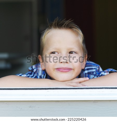 little boy pondering in window sill - stock photo