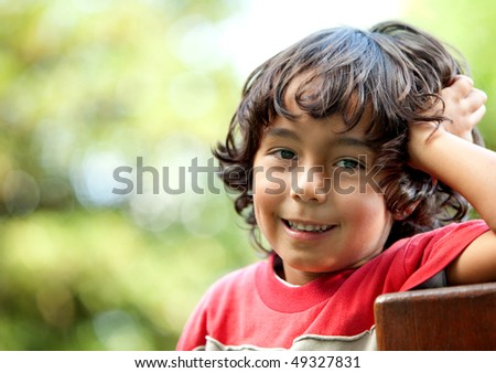 Little boy portrait at the park smiling - stock photo