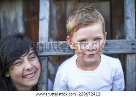 Little boy portrait, older sister fooling around behind in the background. - stock photo