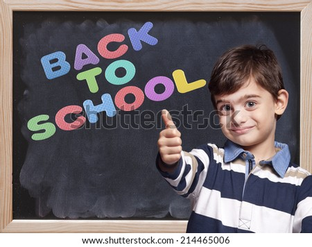 Little boy posing in front of a blackboard with Back to School message - stock photo