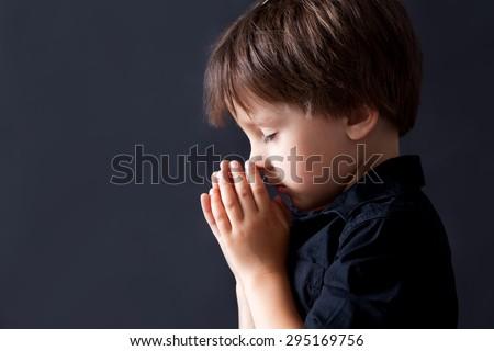 Little boy praying, child praying, isolated black background - stock photo