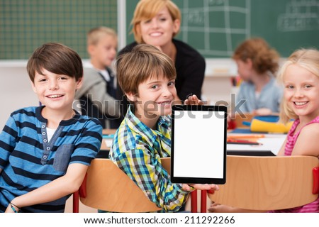 Little boy presenting a blank tablet in class turning in his chair to show it to the camera watched by smiling classmates - stock photo