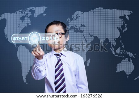 Little boy pressing digital button on a virtual background - stock photo