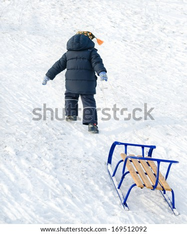 Little boy pulling a blue sled behind him on the snow as he trudges up the slope for a new descent on a cold winter day - stock photo