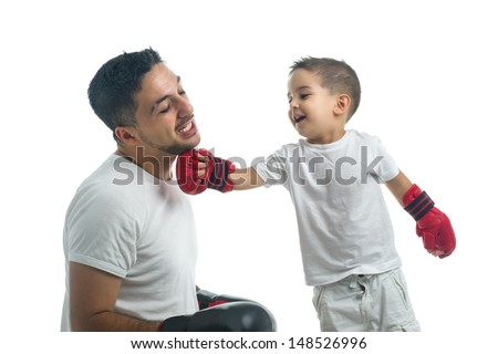 Little boy punching his father with boxing gloves - stock photo