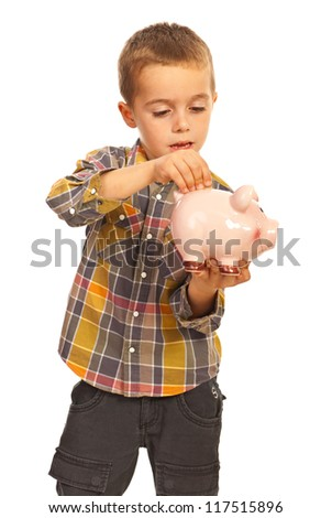 Little boy put a coin into piggy bank isolated on white background - stock photo