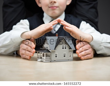 Little boy puts hands as roof over house model. Concept of real estate and protection - stock photo
