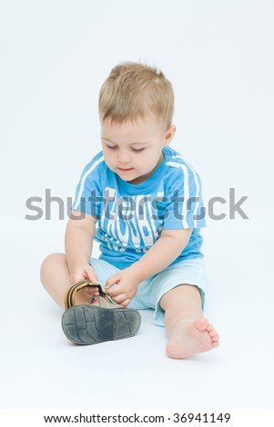 little boy putting his shoes on by himself - stock photo