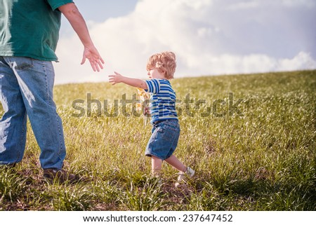 Little boy reaching for his fathers hand - stock photo