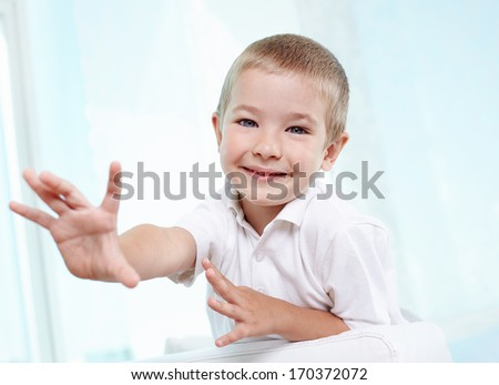 Little boy reaching out towards the camera - stock photo