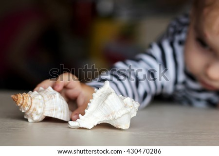 Little boy reaching the sea shell, selective focus, focus on the central shell, dream about summer vacation - stock photo
