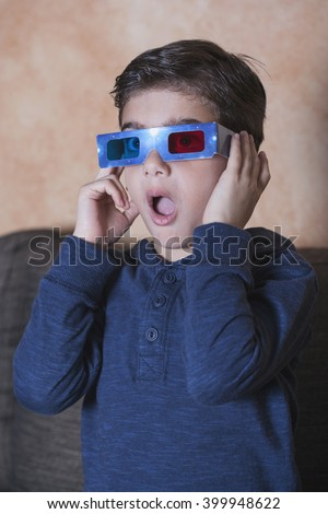 Little boy reacts while watching a 3D movie. Vintage effect image with shallow depth of field