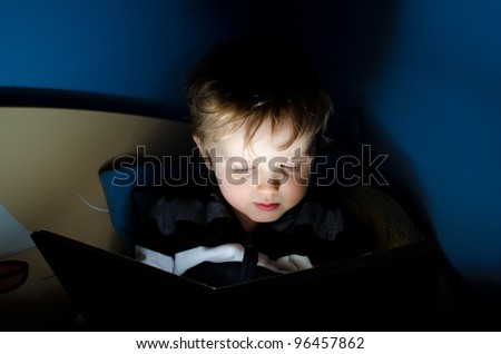 Little boy reading a book in his bed