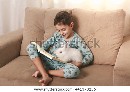 Little boy reading a book with his rabbit at home, sitting on the couch.
