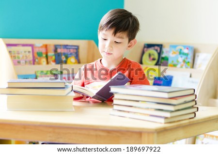 Little boy reading book on table at home - stock photo