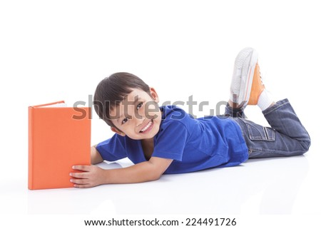 Little boy reading book with lying on the floor - stock photo