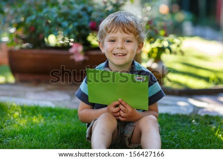Little boy reading his first letter from a friend - stock photo