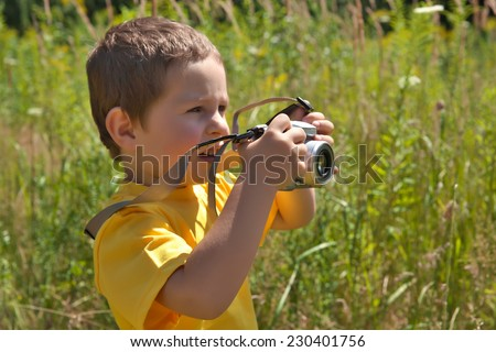 Little boy ready to take picture with his camera