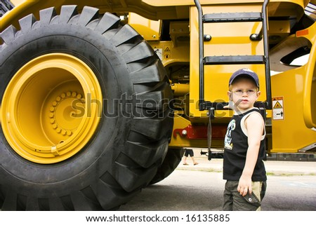 Little boy ready to work on a construction truck - stock photo