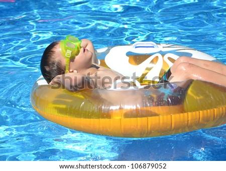 little boy relaxing on pool float - stock photo