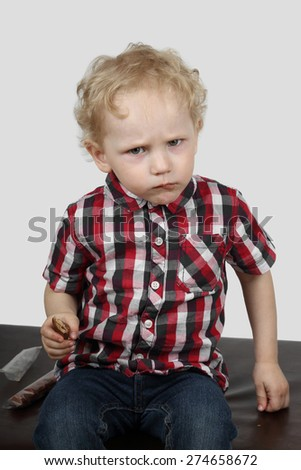 Little boy reluctantly offers candy on gray background - generosity and greed concept - stock photo