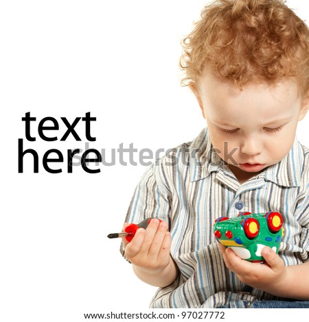 little boy repairs toy car isolated - stock photo