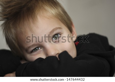 Little boy resting his head on his arms looking at camera with beautiful eyes. - stock photo
