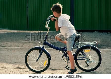Little boy ride on bike outdoors - stock photo