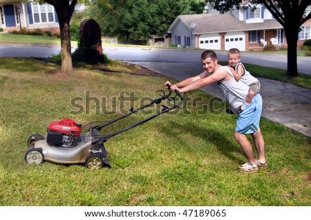 Little boy rides piggy back while dad mows the family's front yard.  Dad is grimacing and child is smiling happily. - stock photo